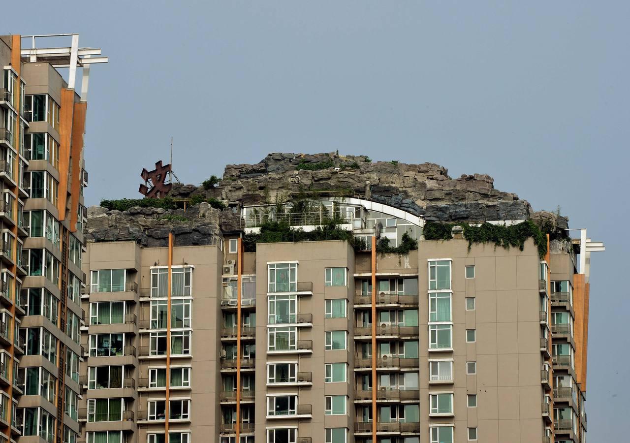 Mansión con vistas, rocas y árboles en lo alto de un rascacielo